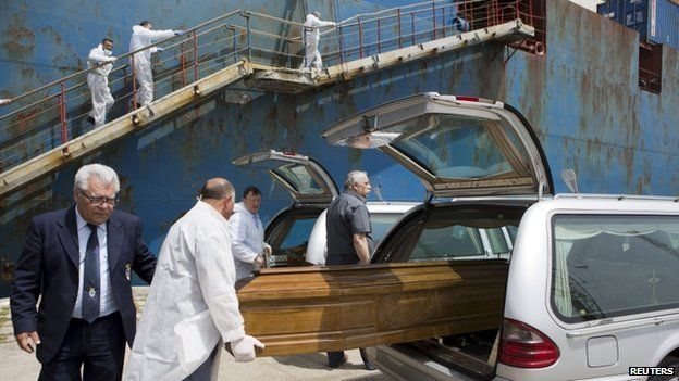 The coffin containing the body of a dead migrant from a merchant ship is put in a car after arriving at the Sicilian harbour of Catania, southern Italy, on 5 May 2015