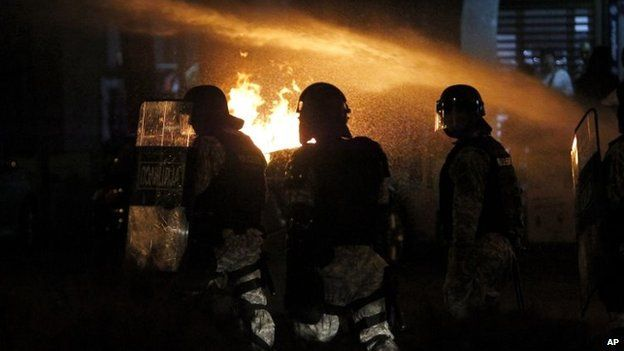 Police officers pass by burning barricades set up on a street by protesters during a protest in Skopje Macedonia, 1 May 2015.