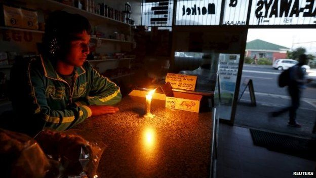 A shopkeeper waits for customers in his candlelit fast food store during a load shedding electricity blackout in Cape Town in South Africa, 15 April 2015