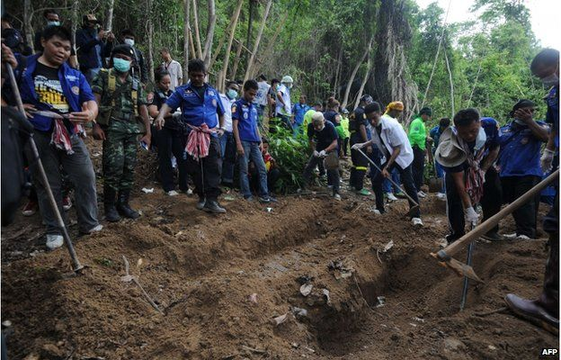 This picture taken on May 2, 2015 shows rescue workers and forensic officials digging out skeletons from shallow graves covered by bamboo at the site of a mass grave at an abandoned jungle camp in the Sadao district of Thailand's southern Songkhla province bordering Malaysia