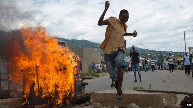 A Burundian protester jumps over a barricade in the Mugasa neighbourhood of Bujumbura on 6 May 2015