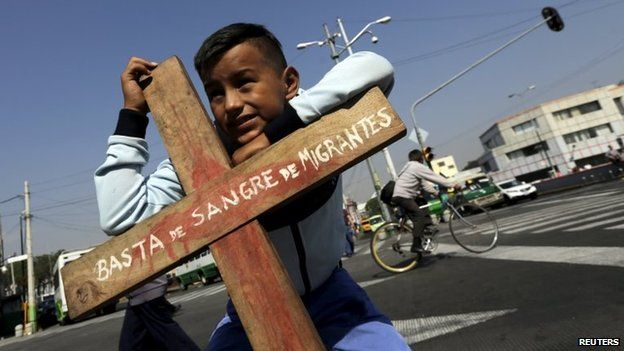 Ten-year-old Marco Carrasco, a migrant from Guatemala, stands outside the Basilica of the Virgin of Guadalupe while holding a cross during an annual human rights protest over Central American citizens crossing overland towards the United States, in Mexico City on 18 April 2015.