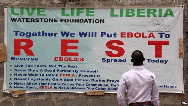 A man reads an Ebola awareness poster near Monrovia