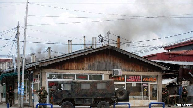 Police officers man a check-point in the conflict zone, as black pillar of smoke is visible behind them, in Kumanovo, northern Macedonia, on May 9, 2015