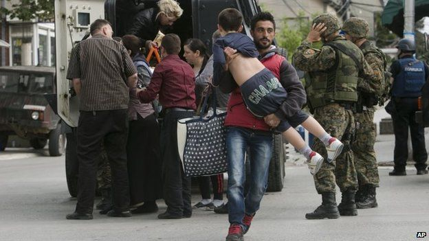 People are evacuated safely from the scene of an altercation involving the police, in northern Macedonian town of Kumanovo, on Saturday, 9 May 2015.