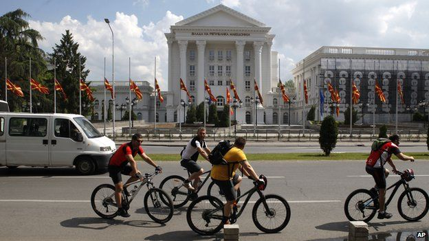 People on bicycles pass in front of the Government building where the national flags are lowered at half mast, in Skopje, Macedonia May 10, 2015