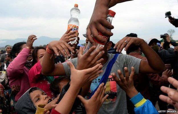 Water is distributed to Nepalese people at a camp set up in the wake of a devastating earthquake in Kathmandu on April 28, 2015.