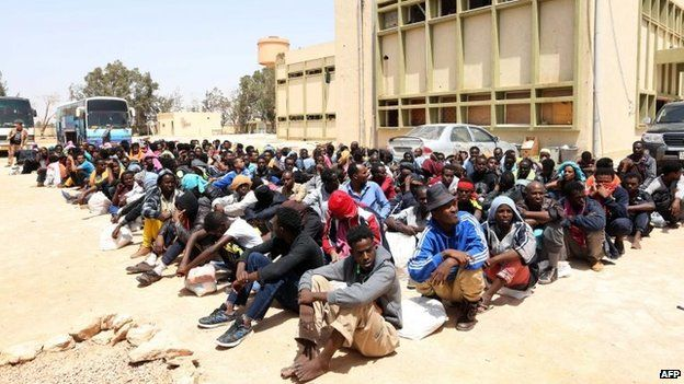 Migrants from sub-Saharan Africa sit at a centre for illegal migrants in the al-Karem district of the Libyan eastern port city of Misrata, 9 May 2015