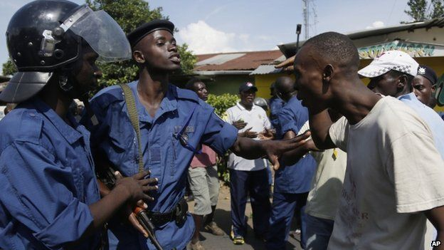 A demonstrator argues with police protesters march through the Musaga district of Bujumbura, in Burundi, Monday, 11 May 2015