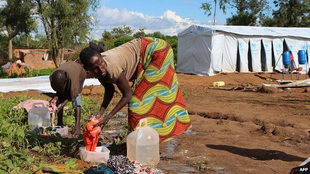 Burundian refugees wash clothes on 9 May 2015 at a temporary shelter at the Gashora refugee camp in the Bugesera district of Rwanda