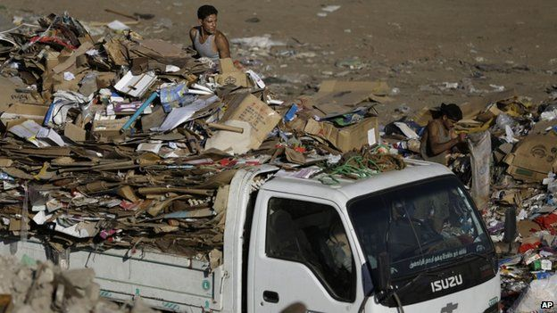 Egyptian rubbish truck collectors on a truck sifting through rubbish in Cairo, Egypt, on 23 October 2014