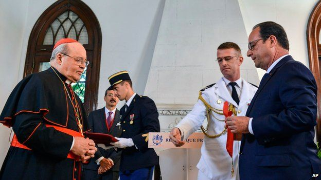 French President Francois Hollande, right, honors Cuban Cardinal Jaime Ortega with the Order Commander of the Legion of Honor at the French Embassy in Havana, Cuba, Monday, May 11, 2015.