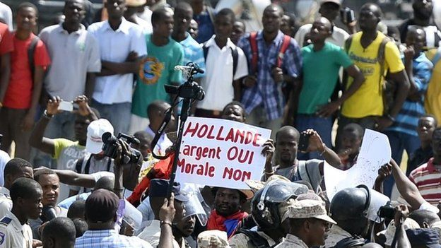"""Protesters in Port-au-Prince hold a banner that reads: """"Hollande: Money Yes, Morals No"""""""