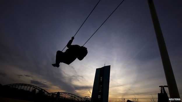 A women rides a swing in a recreation park next the new headquarter of the European Central Bank