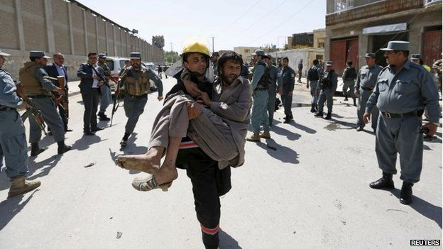 An Afghan policemen carries an injured man after the attack in Kabul (17 May 2015)
