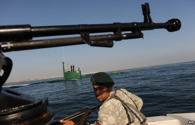 An Iranian Army soldier stands guard on a military speed boat, passing by a submarine during the 'Velayat-90' navy exercises in the Strait of Hormuz in southern Iran on 28 December 2011 as Iran started 10 days of naval drills from 24 December covering east of Strait of Hormuz and the Gulf of Oman to the Gulf of Aden.