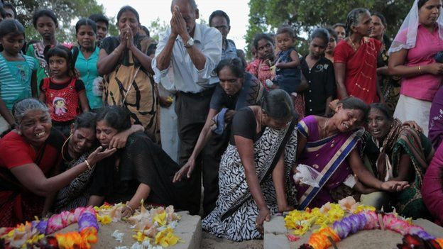 Sri Lankan ethnic Tamil women cry at the grave of their relatives who died in a fierce fighting between the army and Tamil Tiger rebels in Mullivaikkal, about 335 kilometers (208 miles) northeast of Sri Lanka, Monday, May 18, 2015.