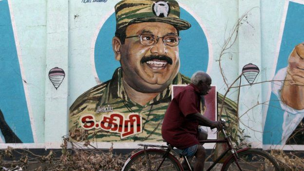 """An Indian elderly man ride his bicycle near a mural of Sri Lanka""""s Liberation Tigers of Tamil Eelam (LTTE) leader Velupillai Prabhakaran on a wall in Chennai, India, Tuesday, May 19, 2015."""