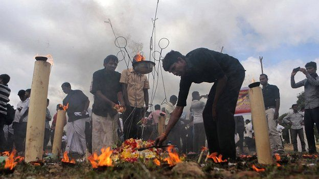 Sri Lanka's ethnic Tamil political activists offer flowers at a makeshift monument, where thousands of people were killed in fierce fighting between the army and Tamil Tiger rebels, in Mullivaikkal. May 18, 2015.