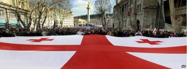 Georgians carry a giant national flag during an opposition rally in Tbilisi