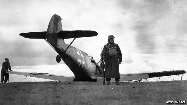A British soldier guarding a German Messerschmitt fighter plane, which was intercepted over the English Channel and shot down by a Spitfire patrol, 27 October 1940