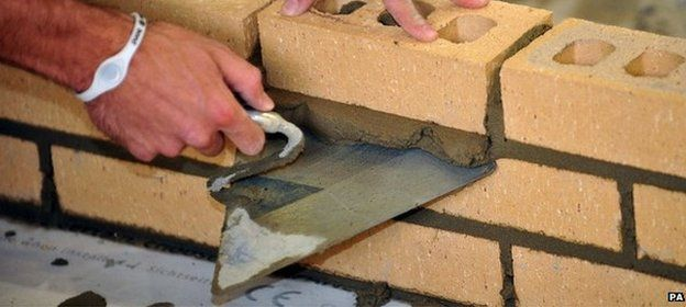 Close up of the hands of a trainee bricklayer, laying bricks