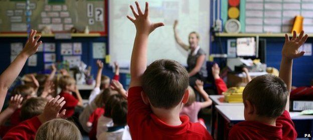 Rear view of primary school children raising their hands in a classroom
