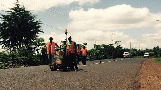 People painting road markings in Nyeri, Kenya