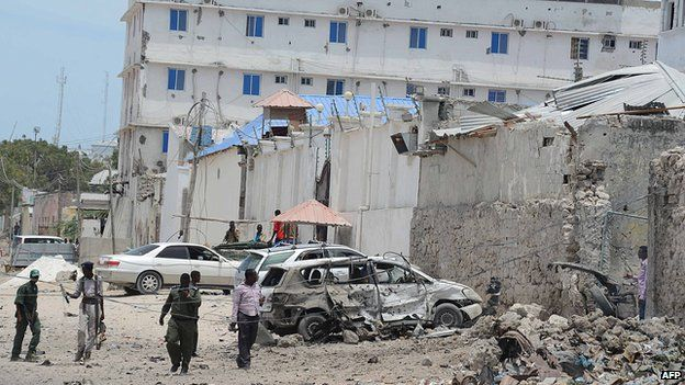Somali government soldiers walk around a destroyed car at the site of car bomb blast in front of the Makka Al Mukarrama Hotel in Mogadishu, on 15 March, 2014.
