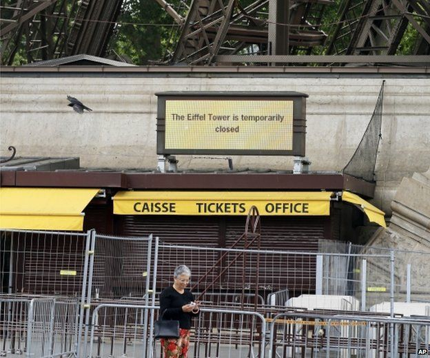 A tourist uses her cell phone under the Eiffel Tower as an information board announces that the Eiffel Tower is temporarily closed, in Paris, 22 May 2015.