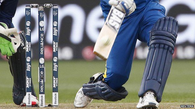 """Sri Lanka""""s captain Angelo Mathews hits the ball for six runs as Scotland""""s wicketkeeper Matt Cross (L) watches during their Cricket World Cup match in Hobart March 11, 2015"""