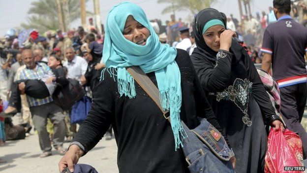 Displaced Sunni women fleeing the violence in Ramadi, carry bags as they walk on the outskirts of Baghdad, 24 May 2015