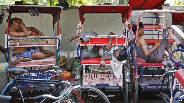 Indian rickshaw pullers sleep in their rickshaws on a hot summer day in New Delhi, India, Thursday, May 21, 2015.