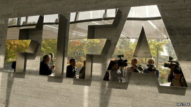 Journalists are reflected in a logo at the FIFA headquarters after a meeting of the executive committee in Zurich on 4 October 2013