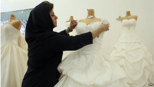 Woman adjusts a wedding dress in a shop in tehran (file photo)