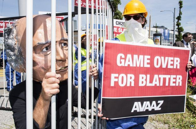 An activist with a giant mask of Fifa president Sepp Blatter stands in a cage as others hold posters during a protest by the Avaaz organization in front of the Hallenstadtion in Zurich, Switzerland, Thursday, 28 May 2015