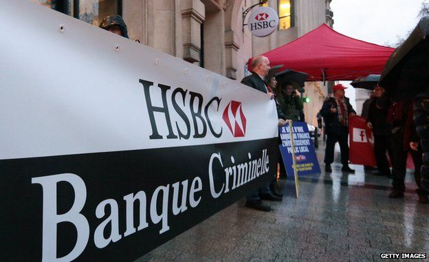 Members of the French Communist party, holding a banner reading 'HSBC, criminal bank' stage a protest outside the headquarters of HSBC on 26 February 2015 in Paris