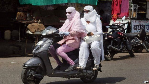 Indian motorcyclists are covered up to protect themselves against the scorching heatwave in Bhopal, India, 28 May 2015.