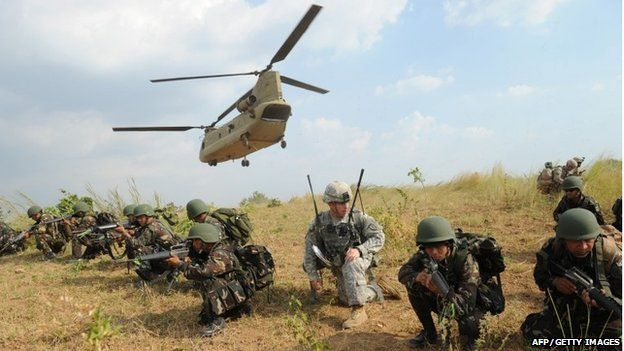 Philippine soldiers and a US army soldier from 2nd Stryker Brigade Combat of the 5th Infantry Division based in Hawaii take their positions after disembarking from a C-47 Chinook helicopter during an air assault exercise inside the military training camp of Fort Magsaysay in Nueva Ecija province north of Manila on April 20, 201
