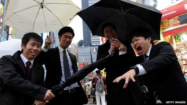 Young salarymen playing on the street while a Godzilla replica is seen behind them in Shinjuku, Tokyo, Japan on 10 April, 2015