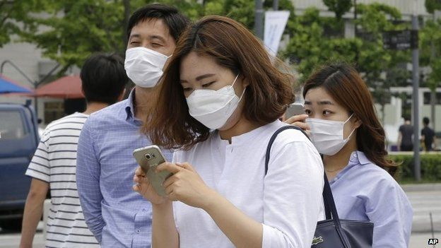 A woman wears a mask as a precaution against Middle East Respiratory Syndrome (MERS) virus as she uses her smartphone on a street in Seoul, South Korea, Tuesday, June 2, 2015.