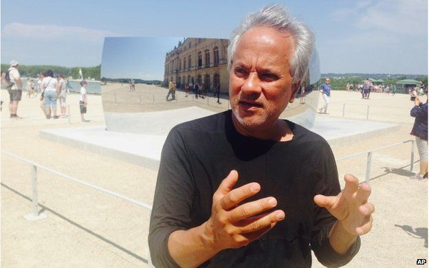 Artist Anish Kapoor answers questions during an interview with the Associated Press during the presentation of his exhibition in the gardens of the Chateau de Versailles near Paris, France, Friday, June 5, 2015
