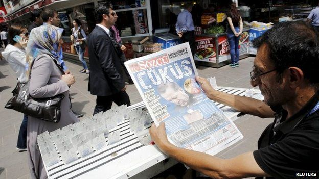 "A lottery ticket vendor reads a Turkish newspaper published with an headline reads ""downfall"" and a portrait of Turkey""s President Tayyip Erdogan in Ankara, Turkey, June 8, 2015"