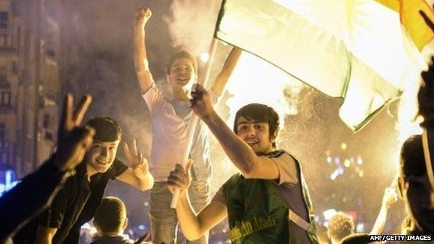 "Supporters of the pro-Kurdish Peoples"" Democratic Party (HDP) hold a Kurdish flag and celebrate in the streets the results of the legislative election, in Diyarbakir on June 7, 2015."