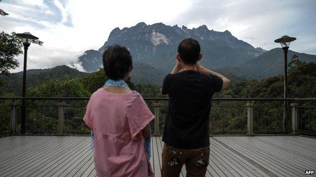 Tourists take pictures of Malaysia's Mount Kinabalu