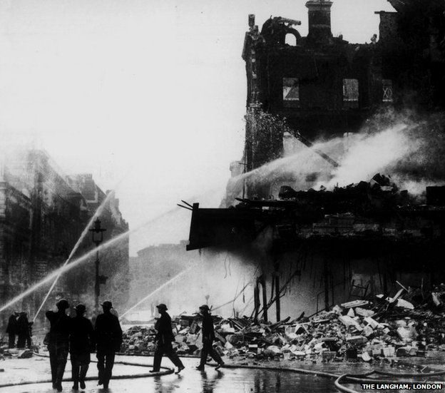 Firefighters douse water on the hotel after it was bombed