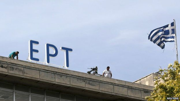 A Greek national flag flutters next to the newly installed logo of the Hellenic Broadcasting Corporation (ERT) in Athens June 8, 2015. ERT