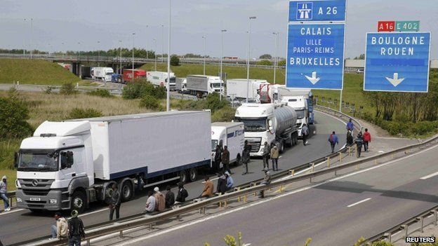 More than a dozen migrants gather near trucks which wait on the road that leads to the Channel tunnel in the hopes of boarding them to make a clandestine crossing to England