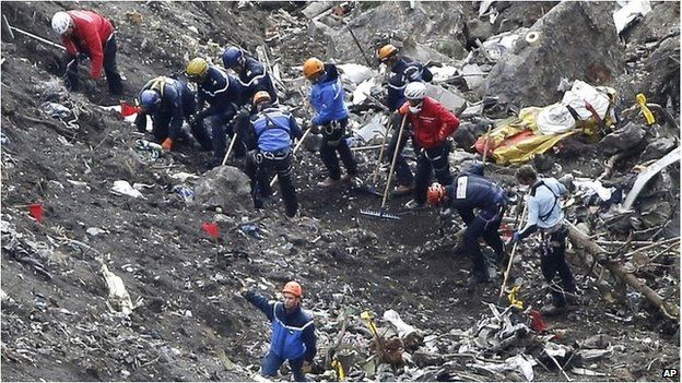 Rescue workers work on debris of the Germanwings jet at the crash site