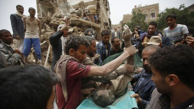 People carry the body of a man they uncovered from under the rubble of houses